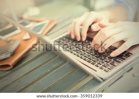 Hands typing on laptop and smart phones on his side - work anywhere concept (selective focus) - stock photo