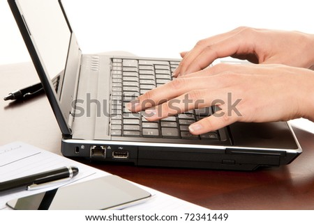 Hands typing on laptop computer keyboard in an office at a workplace near notebook, pen, cellphone isolated on a white background - stock photo