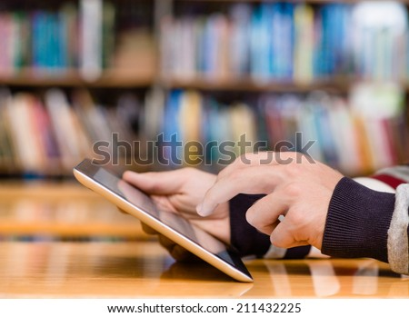 Hands typing on tablet computer in library - stock photo