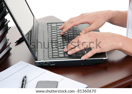 Hands typing on the laptop computer keyboard in an office at a workplace isolated on a white background