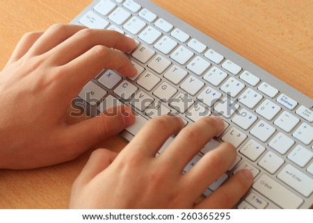 hands typing on the white wireless keyboard - focus on the left hand index finger - stock photo