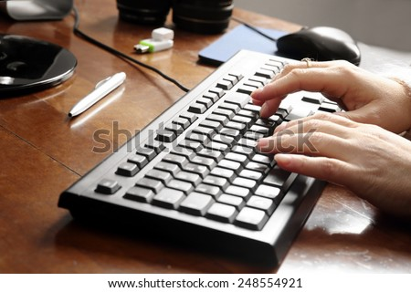hands typing over keyboard at work station - stock photo
