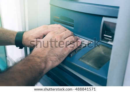 Hands typing PIN at ATM machine for cash money withdrawal