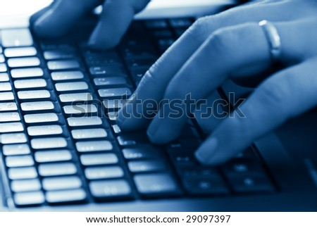 hands typing with shallow depth of field blue toned