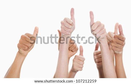 Hands up and thumbs raised against white background - stock photo