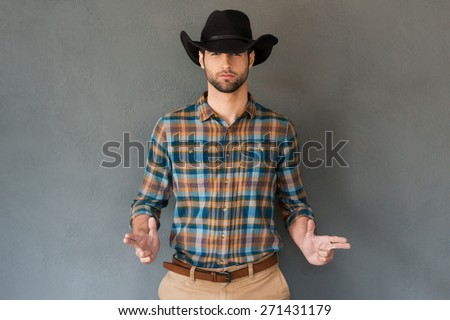 Hands up! Handsome young man wearing cowboy hat and gesturing while standing against grey background  - stock photo