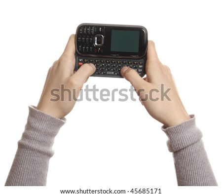 Hands using a black cell phone with a blank screen, isolated on white.
