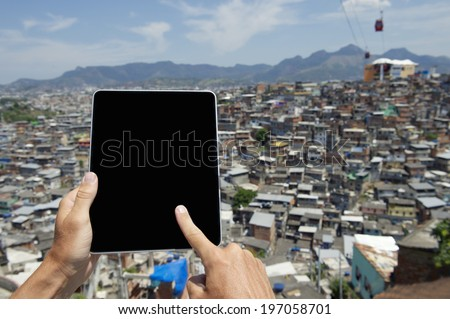 Hands using blank digital tablet computer in front of Brazilian urban slum favela Complexo Alemao in Rio de Janeiro - stock photo