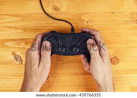 Hands using gamepad controller on wooden desk, flat lay top view, gaming and entertainment concept - stock photo