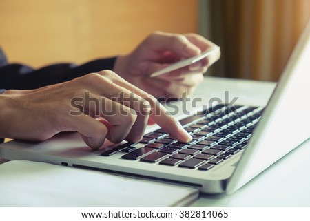 hands using laptop and holding credit card with Online shopping concept in morning light at office