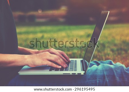 Hands using laptop and typing outside on nature background - stock photo