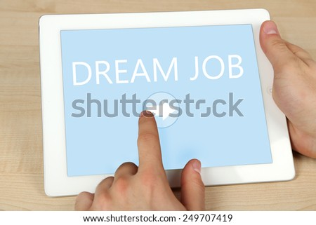 Hands using tablet PC on wooden table background, Job searching concept - stock photo