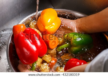 Hands wash vegetables in basin. Red paprika and carrot. Live a healthy life. No pesticides or chemicals. - stock photo