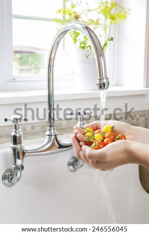 Hands washing fresh cherry tomatoes in running water of kitchen sink with curved faucet - stock photo