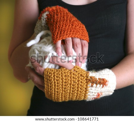 Hands wearing handmade wrist warmers and holding giant ball of yarn - stock photo
