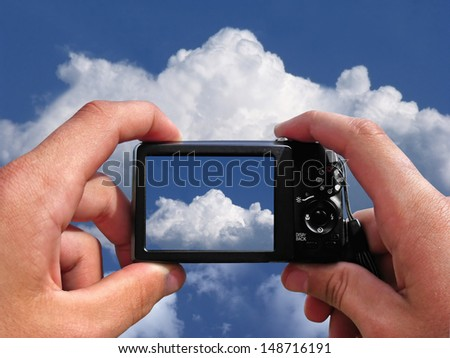 Hands with a camera on the background of the cloudy sky - stock photo