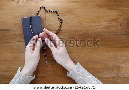 Hands with black rosary folded in prayer over old Holy Bible. Wooden background. - stock photo
