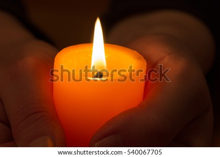 hands with burning candle