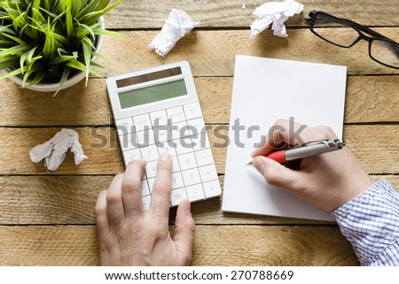Hands with Calculator and notepad. Hands with Calculator, notepad, pen and green plant on wooden background - stock photo