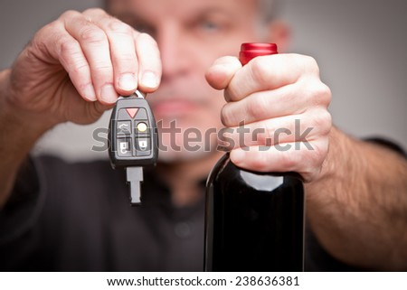 hands with car keys and a bottle of wine symbolizing alcohol problems and accidents - stock photo