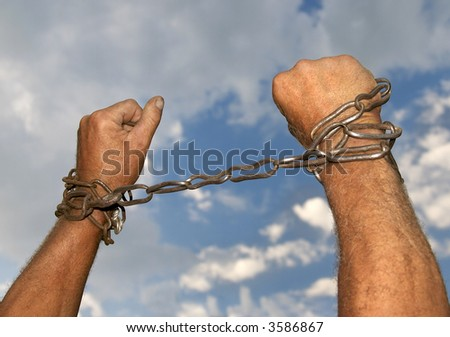 Hands with chains around them on sky background