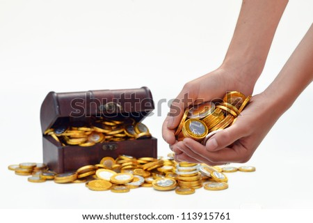 Hands with chocolate candy euro coins and a treasure chest in the background. - stock photo