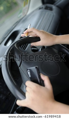 hands with cigarette and mobile phone  in the car - stock photo