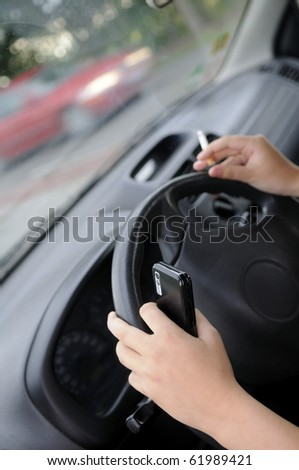 hands with cigarette and mobile phone  in the car