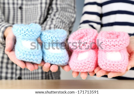 Hands with crocheted booties for baby, close-up - stock photo