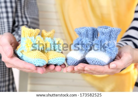 Hands with crocheted booties for baby, on light background - stock photo