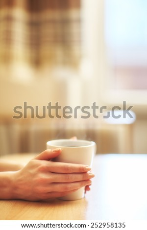 Hands with cup of hot morning coffee on the table with window in background - stock photo