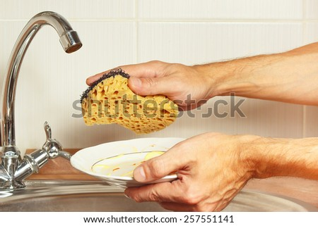 Hands with dirty dishes over the sink in the kitchen - stock photo
