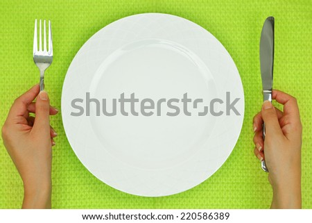 Hands with fork and knife and empty plate on the table - stock photo
