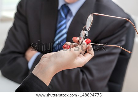 Hands with glasses and an angry businessman