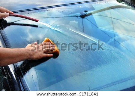 hands with hose and sponge washing blue car glass - stock photo
