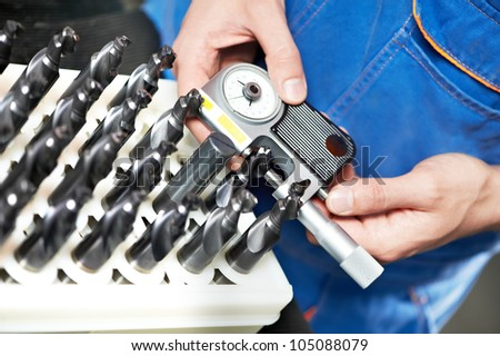 Hands with industrial micrometer gauge measuring work piece of mill cutter or tool at manufacture workshop - stock photo