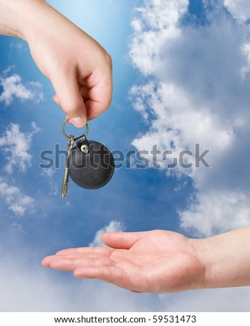 hands with key over blue sky background - stock photo