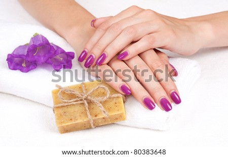 Hands with manicure lying down on towel with soap and flowers - stock photo