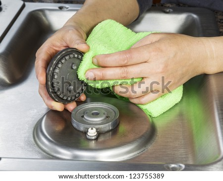 Hands with microfiber cloth cleaning gas stove burner cover - stock photo
