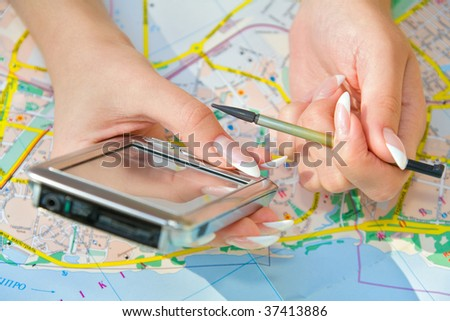 Hands with mobile computer device and stylus over city map - stock photo
