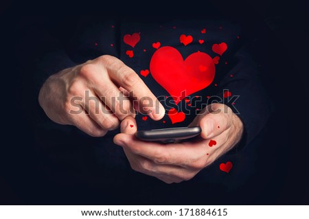 Hands with mobile phone and hearts. Man typing love text message on smartphone for Valentine's day. - stock photo