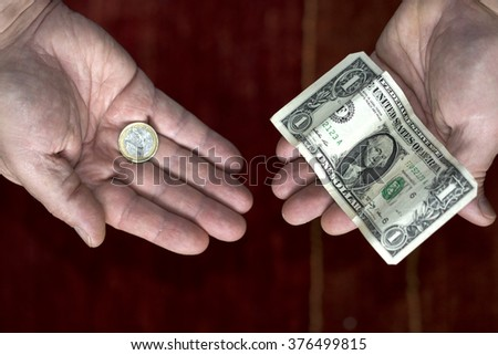 Hands with one dollar and one euro