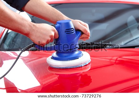 Hands with orbital polisher in auto repair shop. - stock photo