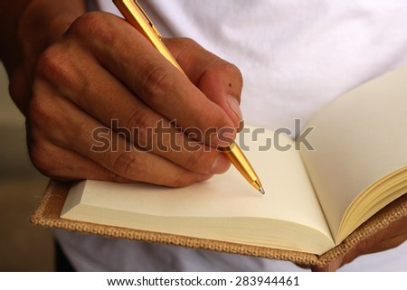 Hands with pen over note paper - stock photo