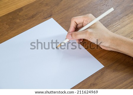 Hands with pen over paper isolated on white paper - stock photo