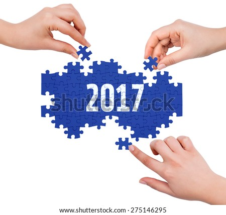 Hands with puzzle making 2017 word  isolated on white  - stock photo