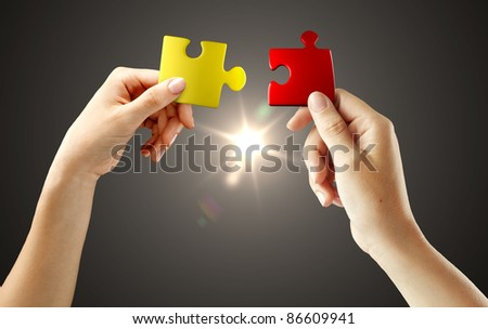 Hands with puzzle on black background. Teamwork solving a puzzle