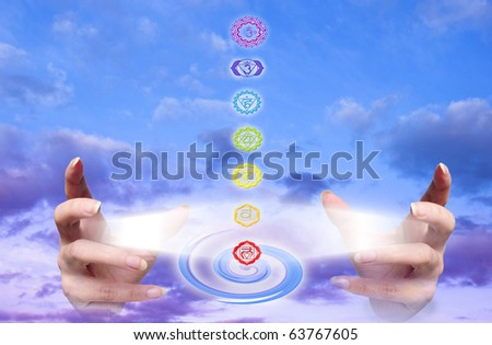 hands with rays of light and seven chakra like a concept of healing hands - stock photo