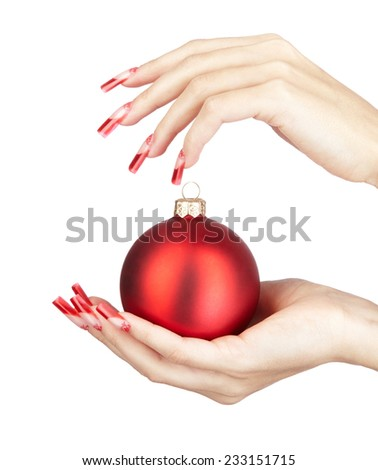 Hands with red french false acrylic nails manicure holding christmas ball isolated on white background - stock photo