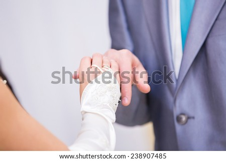 Hands with rings Groom putting golden ring on bride's finger during wedding ceremony Loving couple - stock photo
